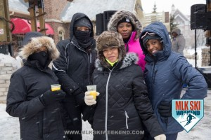 MLK Ski Weekend 2016 group photo of ladies posing outside in winter gear having a drink in the village