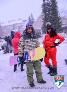 MLK Ski Weekend snowboard black snowboarder and girl in snowsuit while snowing